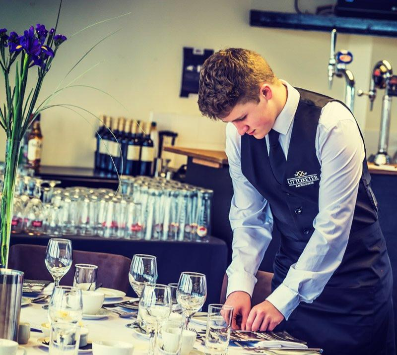 A waiter setting up a table in restaurant at Uttoxeter Racecourse.