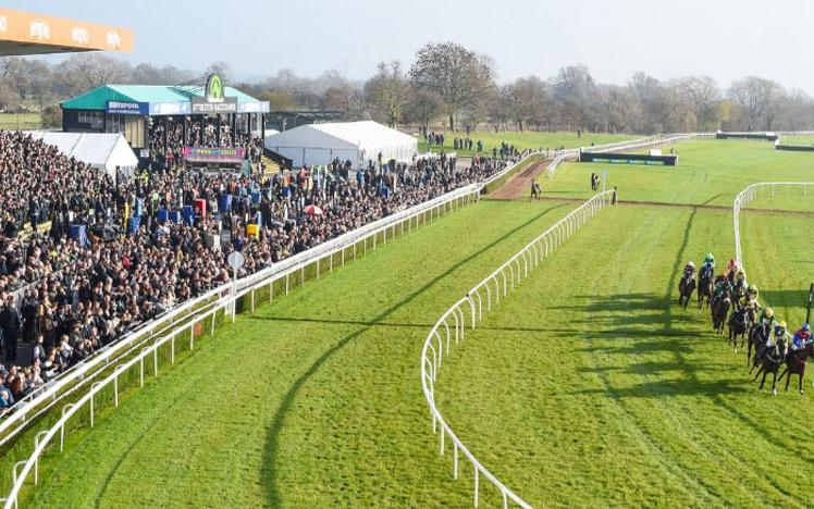 Crowds gathered at Uttoxeter Racecourse watching racing action on the track.