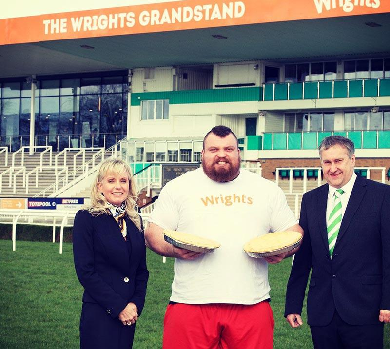 A strongman competitor posing for a photo with member of the Uttoxeter team.