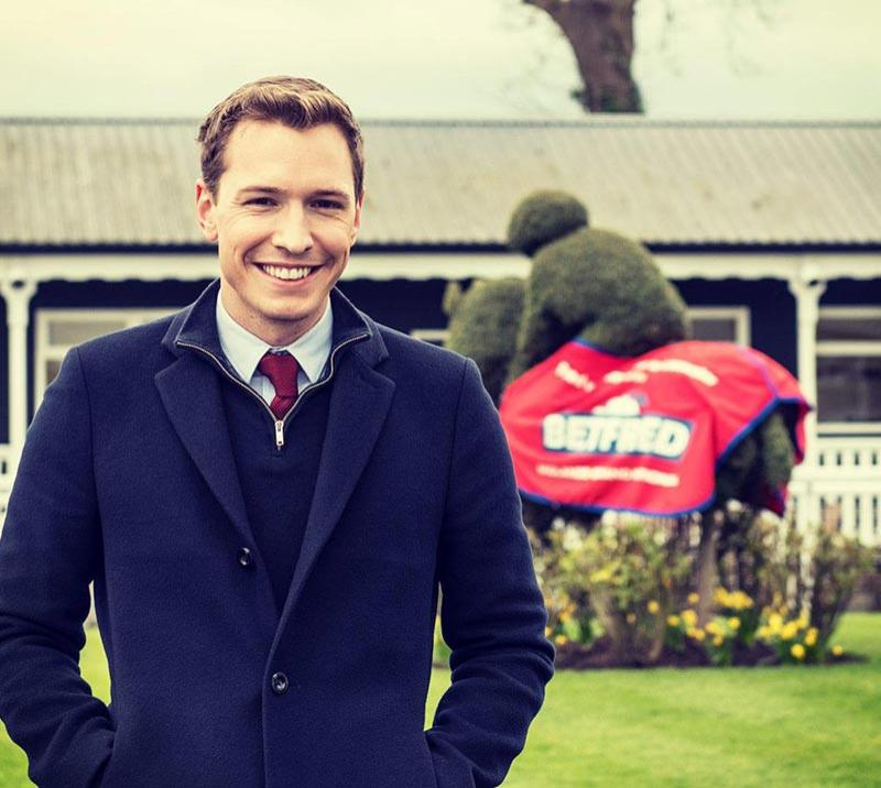 Gentleman posing for a photo with the parade ring behind him.